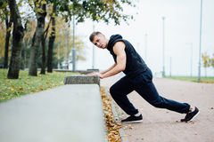 Male runner doing exercise, workout in the fall park. Push ups with bench. Male runner doing exercise, preparing for morning workout in the fall park. Push ups Stock Image