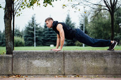 Male runner doing exercise, workout in the fall park. Push ups with bench. Male runner doing exercise, preparing for morning workout in the fall park. Push ups Royalty Free Stock Image