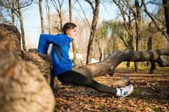 Male Runner Doing Push Up on the Log in the Park in Sunny Autumn Morning. Healthy Lifestyle and Sport Concept. Young Male Runner Doing Push Up on the Log in the Royalty Free Stock Photography