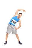 Male runner doing stretching exercise. Full length portrait of a young male runner in a blue tank top doing stretching exercise and looking at the camera Royalty Free Stock Photo