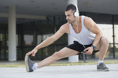 Male runner doing stretching exercise. Preparing for morning workout outdoors. While doing a stretching exercise, he listens to music and holds a mobile phone Royalty Free Stock Photography