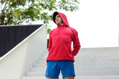Male runner doing stretching exercise,. Preparing for morning workout in the park Stock Photo
