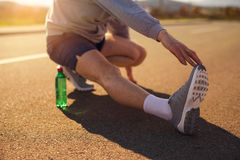 Male runner doing stretching exercise. Selective focus Royalty Free Stock Photo