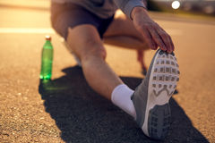 Male runner doing stretching exercise. Selective focus Royalty Free Stock Photography