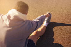 Male runner doing stretching exercise. Selective focus Stock Photo