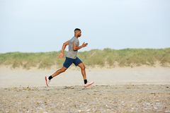 Male runner exercising on the beach. Side view of a male runner exercising on the beach Stock Images