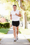 Male Runner Exercising On Suburban Street. Running Towards Camera Stock Photos