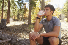 Male runner in a forest takes a break to sit and drink water Stock Photo