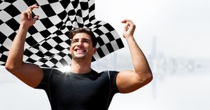 Male runner with hands in air against white skyline and checkered flag. Digital composite of Male runner with hands in air against white skyline and checkered Royalty Free Stock Photo