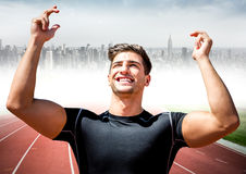 Male runner with hands in air on track against blurry skyline. Digital composite of Male runner with hands in air on track against blurry skyline Royalty Free Stock Image