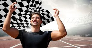 Male runner with hands in air on track against flares and checkered flag. Digital composite of Male runner with hands in air on track against flares and Royalty Free Stock Image
