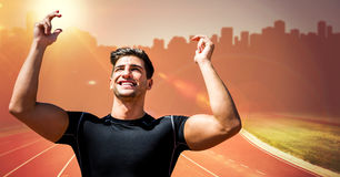 Male runner with hands in air on track against orange flare and blurry skyline. Digital composite of Male runner with hands in air on track against orange flare Stock Photography