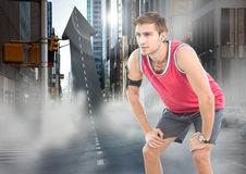 Male runner with headphones on arrow shaped road in street. Digital composite of Male runner with headphones on arrow shaped road in street Stock Photo