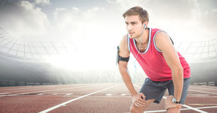 Male runner with headphones on track against flares. Digital composite of Male runner with headphones on track against flares Royalty Free Stock Photos