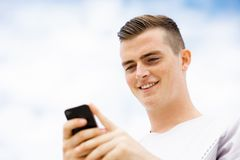 Male runner with his mobile smart phone standing outdoors. Young male runner with his mobile smart phone standing outdoors Stock Image
