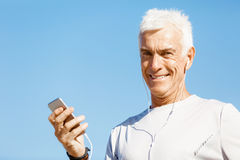 Male runner with his mobile smart phone standing outdoors. Young male runner with his mobile smart phone standing outdoors Stock Images