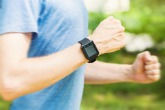 Male runner jogging outside with his smart watch Royalty Free Stock Photos