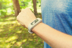 Male runner jogging outside looking at his wearable fitness tracker Royalty Free Stock Photos