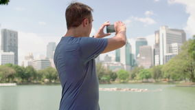 Male runner jogging in park. Fit male sport fitness training. Making photo on his smartphone. Handsome young man runner jogging in park. Fit male sport fitness stock video