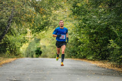 Male runner leader of race running in autumn Park, yellow leaves on ground Royalty Free Stock Photo
