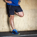 Male runner leaning against wall. Male runner leaning relaxed against wall Royalty Free Stock Image
