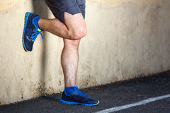 Male runner leaning relaxed. Against wall Stock Images