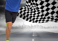 Male runner legs on road with skyline against storm and checkered flag. Digital composite of Male runner legs on road with skyline against storm and checkered Stock Image