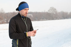 Male runner listen music from smartphone on winter day. Male runner enjoying outside on snow after running on winter day and listen music in earphones from Royalty Free Stock Images
