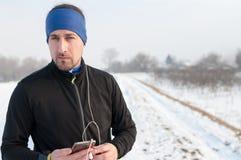 Male runner listen music from smartphone on winter day. Male runner enjoying outside on snow after running on winter day and listen music in earphones from Stock Image