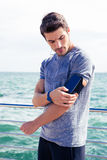 Male runner listening to music adjusting settings on armband for smartphone Stock Images