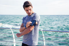 Male runner listening to music adjusting settings on armband for smartphone Royalty Free Stock Images