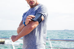 Male runner listening to music adjusting settings on armband for smartphone Royalty Free Stock Photography