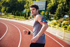 Male runner listening to music with mobile phone. At the stadium and looking at camera Royalty Free Stock Photography