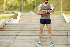 A male runner looks at a smart watch on his arm.  Royalty Free Stock Photos