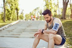 A male runner looks at a smart watch on his arm.  Stock Photos