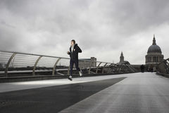 Male Runner On Millennium Bridge With St Paul's Behind Royalty Free Stock Image
