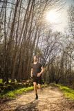 Male runner on nature. Road in misty forest full of pleasure warm light Royalty Free Stock Images