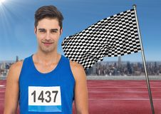 Male runner with number on shirt on track against skyline and checkered flag. Digital composite of Male runner with number on shirt on track against skyline and Royalty Free Stock Photo