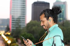Male runner plays with smart phone before run in the city - Stock image.  Royalty Free Stock Photo