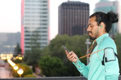 Male runner plays with smart phone before run in the city - Stock image.  Stock Photography