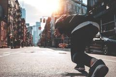 Male runner preparing to run straight through Manhattan streets. Athlete man in running start pose on urban street. Male runner preparing to run straight through stock image