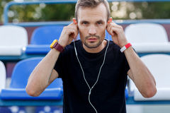 Male runner putting headphone in his ears standing on stadium Royalty Free Stock Images