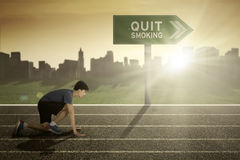 Male runner with quit smoking word on signpost. While ready to run in the track stock photography
