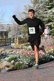Male runner in race. Male runner on garden pathway with tulip flowers after a recent snow in spring Royalty Free Stock Images