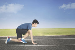 Male runner in ready position to run. While kneeling in the line start on the track Royalty Free Stock Photo