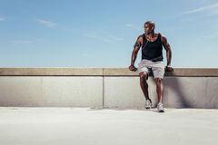 Male runner relaxing on embankment looking away copyspace Royalty Free Stock Photography