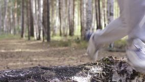 Male runner running along a nature trail through the woods. Athlete running through the woods. Feet, bottom view stock footage