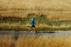 Male runner running on asphalt road. In blue jacket and black tights Stock Photos