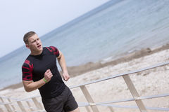 Male runner running on the beach. Closeup of a young male runner is running on the beach - focus on the face Royalty Free Stock Images