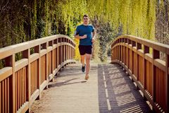 Male runner running in a city park over a bridge training royalty free stock photos